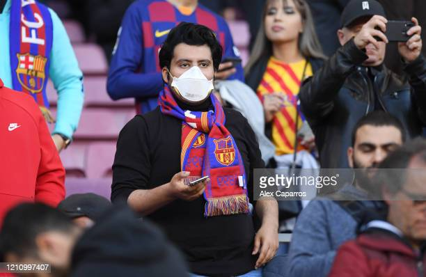 Fans wear health mask in the crowd prior to the La Liga match between FC Barcelona and Real Sociedad at Camp Nou on March 07, 2020 in Barcelona,...