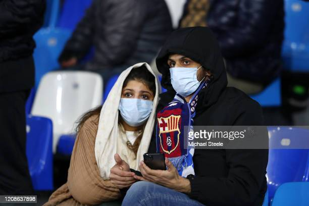 Fans wear medical face masks as they await kick off prior to the UEFA Champions League round of 16 first leg match between SSC Napoli and FC...