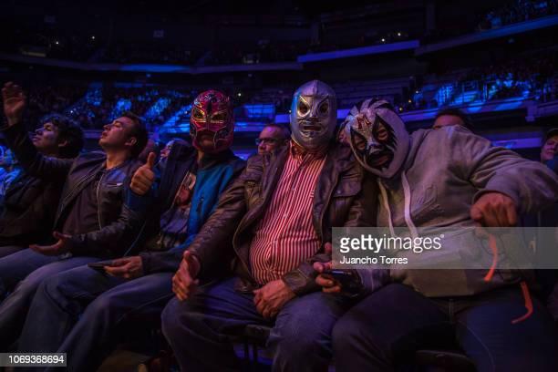Fans wear wrestling masks during an AAA World Wide Wrestling match on November 16 2018 in Bogota Colombia