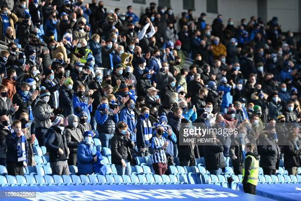 Fans wearing a face masks or coverings due to the COVID-19 pandemic, sit socially distanced as they wait for kick off in the English Premier League...