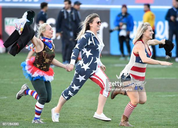 Fans wearing costumes run on the pitch during the Cup Final match between the United States and Argentina during the USA Sevens Rugby tournament at...