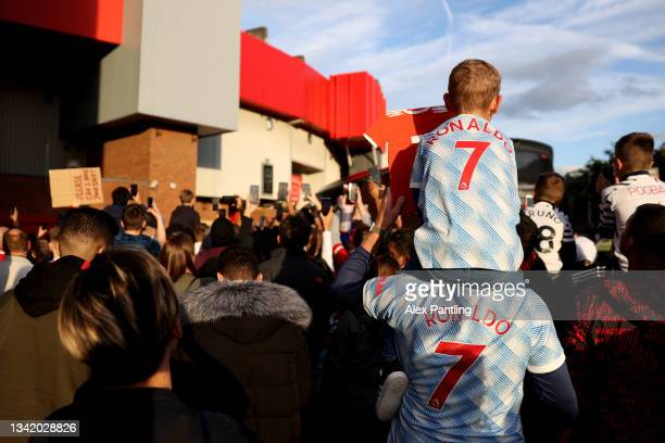 Fans wearing Cristiano Ronaldo shirts await the arrival of the team bus during the Carabao Cup Third Round match between Manchester United and West...