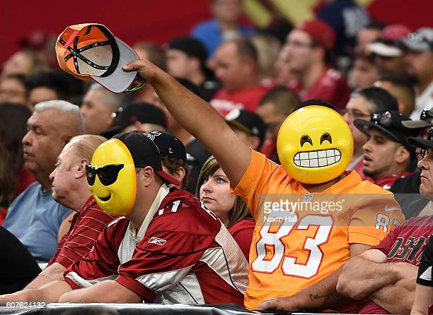 Fans wearing emoji masks wave during the second half of the NFL game between the Arizona Cardinals and the Tampa Bay Buccaneers at University of...