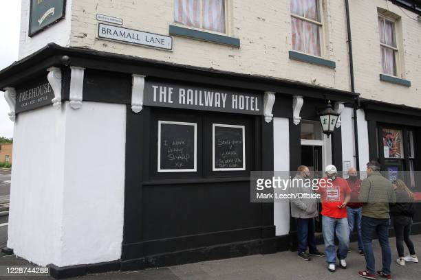 Fans wearing face masks leave The Railway Hotel pub ; chalk boards outside the pub show positive messages about Sheffield United ahead of the Premier...