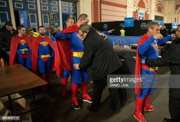 TOPSHOT Fans wearing fancy dress are searched as they arrive ahead of the PDC World Championship darts final between Netherlands' Michael van Gerwen...