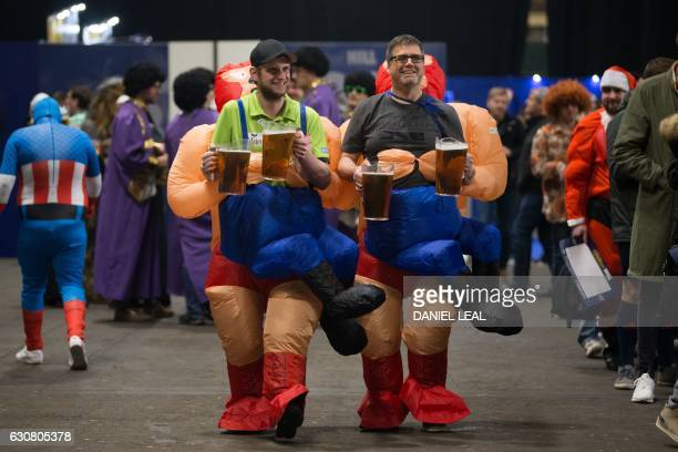 Fans wearing fancy dress costumes collect their beer ahead of the PDC World Championship darts final between Netherlands' Michael van Gerwen and...