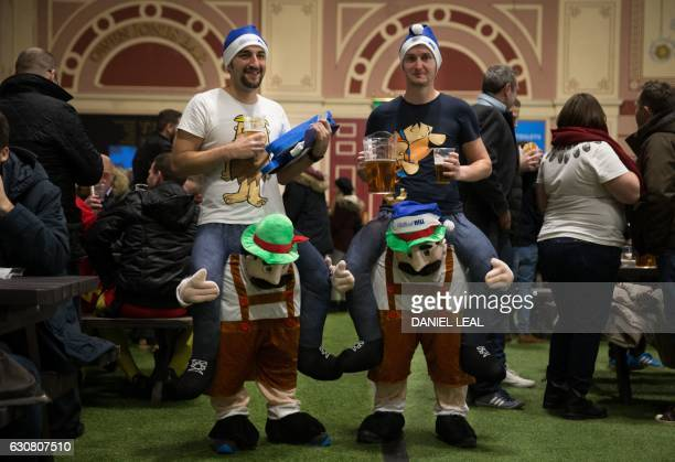 Fans wearing fancy dress pose for a photograph as they enjoy a beer ahead of the PDC World Championship darts final between Netherlands' Michael van...