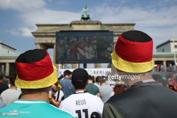 Fans wearing hats in the colors of the German flag arrive in front of the Brandenburg Gate at the Fanmeile public viewing area to watch the Germany...