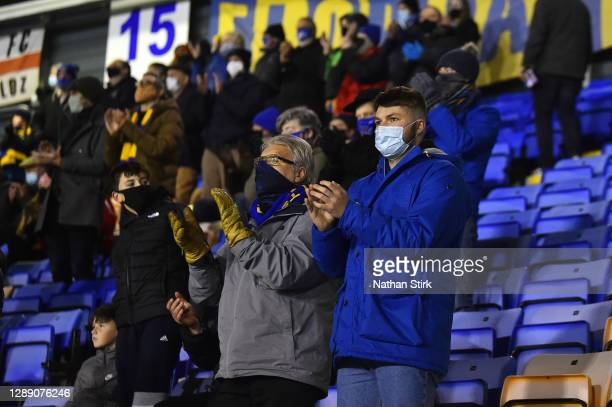 Fans wearing masks applaud whilst standing socially distant during the Sky Bet League One match between Shrewsbury Town and Accrington Stanley at...