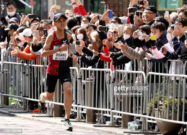 Fans wearing masks cheer Suguru Osako of Japan despite the organiser's recommendation not to attend during the Tokyo Marathon on March 1 2020 in...