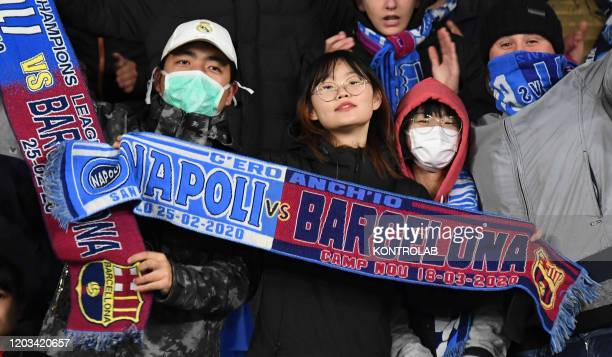Fans wearing masks for fear of coronavirus infection at the San Paolo Stadium in Naples during the football match UEFA Champions League SSC Napoli vs...