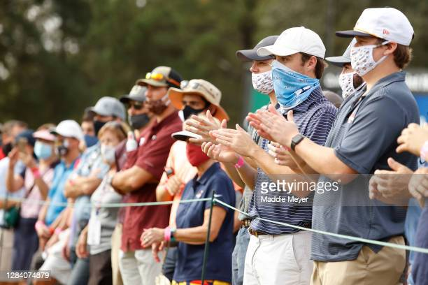 Fans, wearing masks, watch action on the ninth green during the first round of the Vivint Houston Open at Memorial Park Golf Course on November 05,...