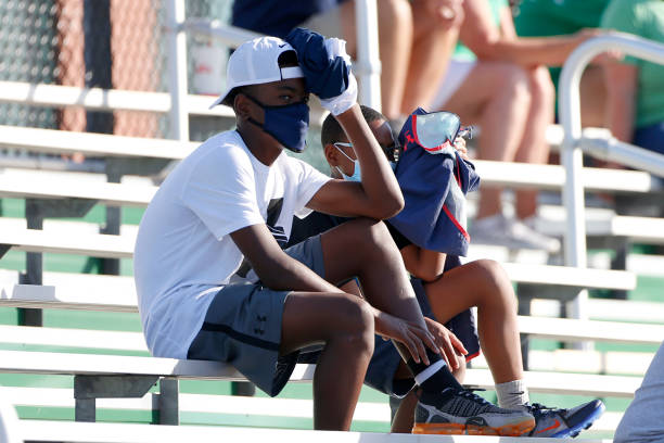 Fans wearing masks watch the action from the stands during the game between the Cathedral Fighting Irish and the Westfield Shamrocks on August 21,...