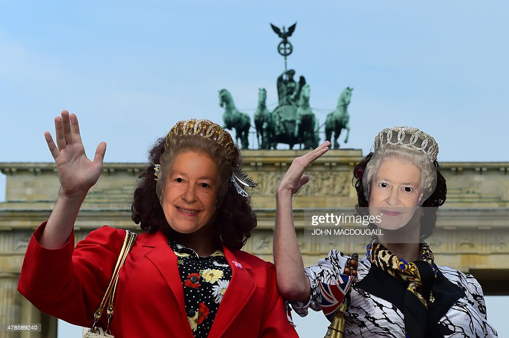 Fans wearing masks with the image of Britain's Queen Elizabeth II pose in front Berlin's landmark Brandenburg Gate on June 26, 2015, after the Queen left Berlin. British Queen Elizabeth II ends her three-day visit to Germany.