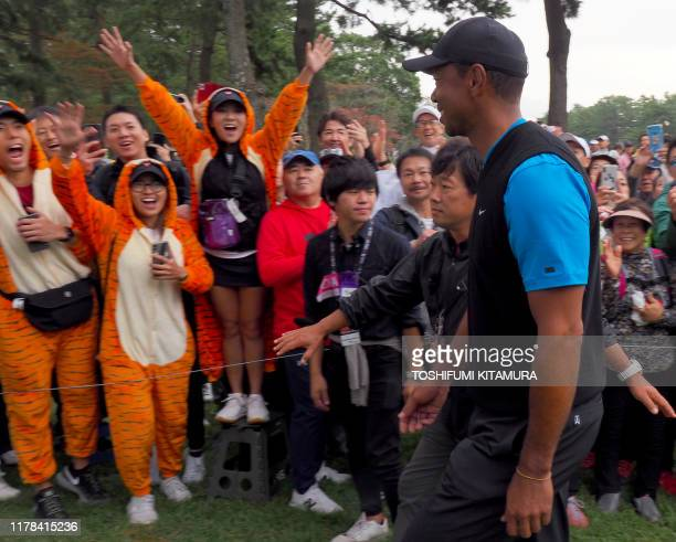 Fans wearing tiger costumes welcome Tiger Woods of the US during the third round of the PGA Zozo Championship golf tournament at the Narashino...