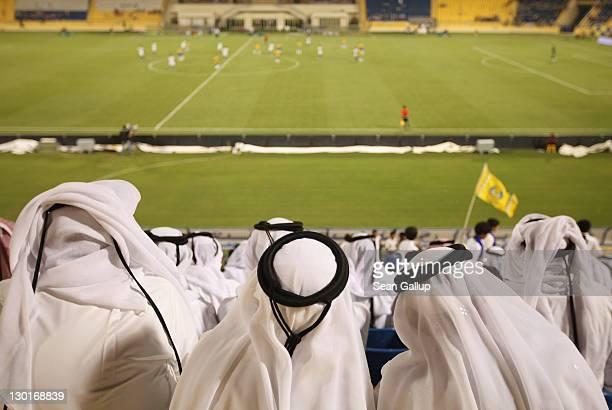 Fans wearing traditional local dress attend the Gharafa vs. Kharaitiyat Qatar Stars League football match at Al Gharafa Stadium on October 23, 2011...