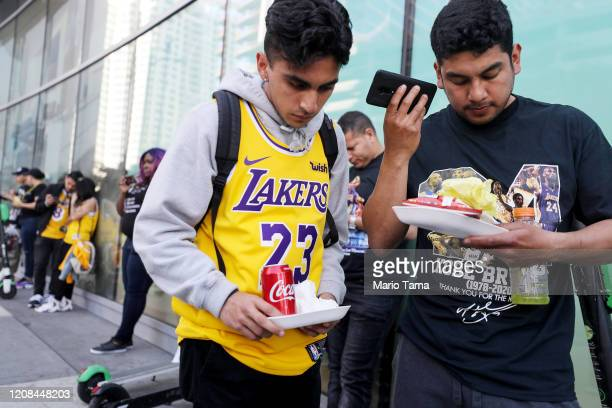 Fans who didn't have tickets listen to a live broadcast of the 'Celebration of Life for Kobe and Gianna Bryant' memorial service on their phones...