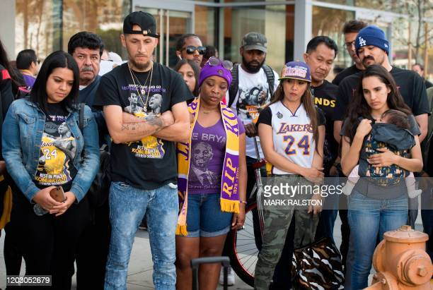 Fans who were unable to get tickets react as they watch the Celebration of Life for Kobe and Gianna Bryant service on an mobile device outside the...