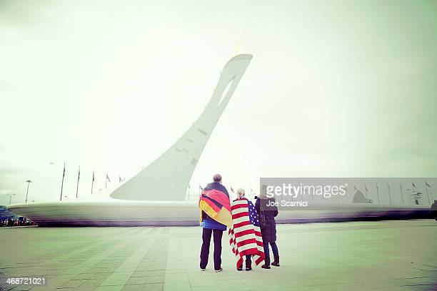 Fans with a German and an American flag pause in front of the Olympic Cauldron in the Olympic Park on Day 4 of the 2014 Winter Olympics on February...