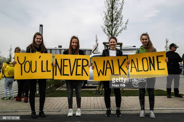 Fans with a sign 'You'll never walk alone' stand next to the Dortmund Brackel Training Ground of Borussia Dortmund prior the UEFA Champions League...