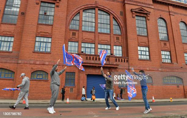 Fans with flags gather outside the stadium as Rangers fans, gather outside the Ibrox Stadium, to celebrate their team winning the Scottish...