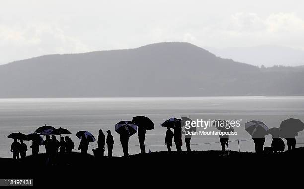 Fans with umbrellas watch the action in the rain on the 18th hole during the second round of The Barclays Scottish Open at Castle Stuart Golf Links...