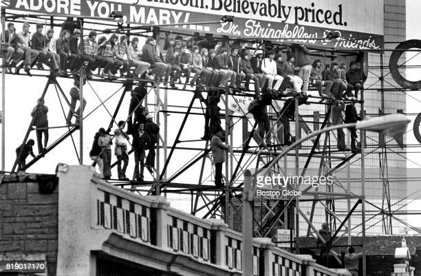 Fans without tickets to Game One of the World Series between the Boston Red Sox and the Cincinnati Reds climb and watch from a billboard on...
