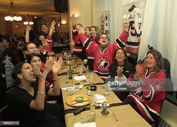 FANS0222/02hockey fans From RBC Investments cheer for Canada in the Bottom Line Bar at 22 Front West they are lr around the table Deepa Gupta Monica...