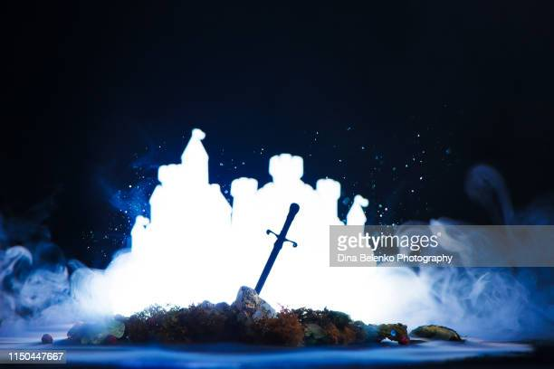 fantasy castle with a silhouette of a legendary sword. camelot and excalibur reference. creative still life with copy space. - fairytale stock pictures, royalty-free photos & images