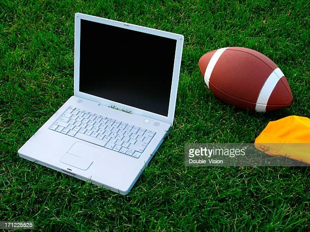 Fantasy Football Concept: Laptop Computer and Football on Grass Field