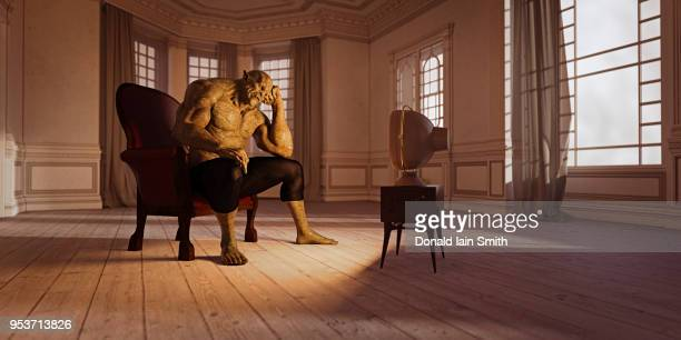 Fantasy troll or ogre sits watching television, resting head, in empty room, with morose look.