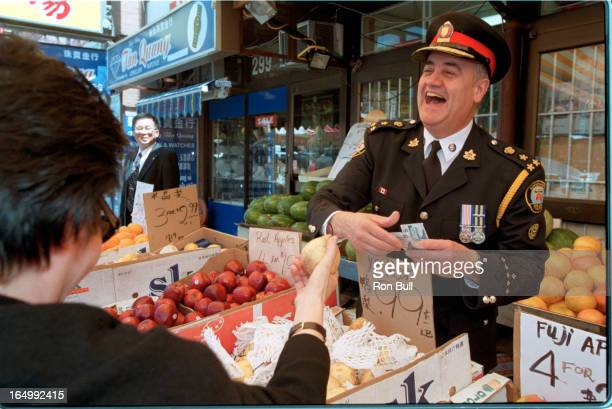 Fantino tours China town Trying his hand as a fruit vendor he offers Mabel Sin of the Chinese consultative committee touring the street with Fantino...