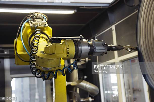 A Fanuc Corp robotic arm holds a faucet part while the component is buffed at a faucet manufacturing plant of HSIL Ltd in Bhiwadi Rajasthan India on...