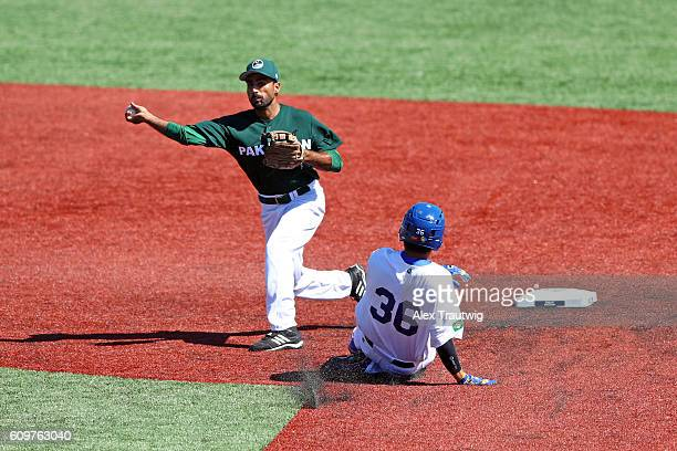 Faquir Hussain of Team Pakistan turns a double play as Reinaldo Sato of Team Brazil slides into second base during Game 1 of the 2016 World Baseball...