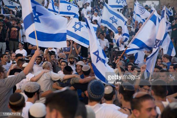 Far right Israelis dance with Israeli flags as they march near Damascus Gate during the flag march on June 15, 2021 in Jerusalem, Israel. Authorities...
