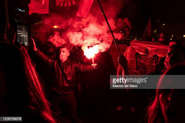 Far right wing supporter making a fascist salute holding a flare and people carrying a pre-constitutional Spanish flag during a rally to commemorate...