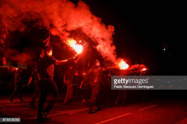 Far right wing supporters hold smoke flares during the 'Crown March' to the Valley of the Fallen to commemorate the 81st death anniversary of Falange...