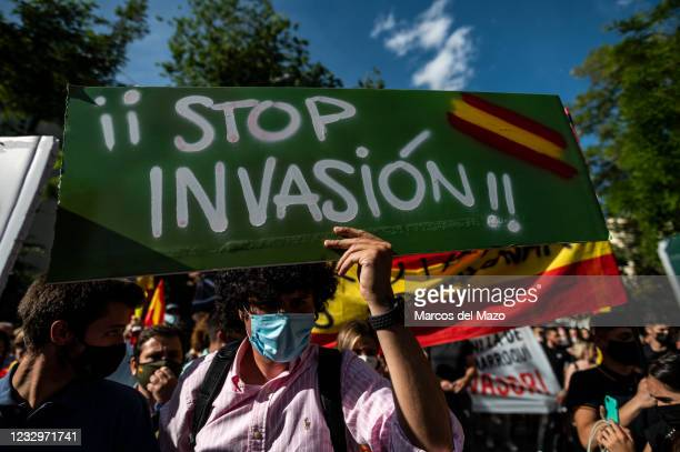 Far right wing VOX party supporter holding a placard reading 'Stop the invasion' protesting in front of the Moroccan Embassy of Madrid called by far...