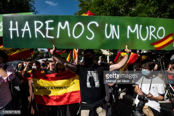 Far right wing VOX party supporter holding a placard reading 'we will make a wall' protesting in front of the Moroccan Embassy of Madrid called by...
