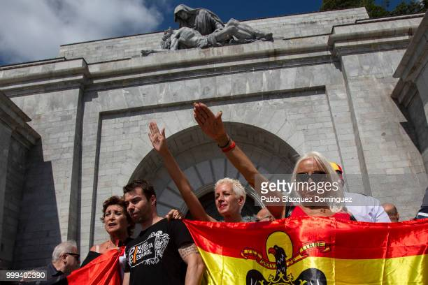 Far rightwing supporters do fascist salutes as they hold a preconstitutional Spanish flag during a gathering at El Valle de los Caidos under the...