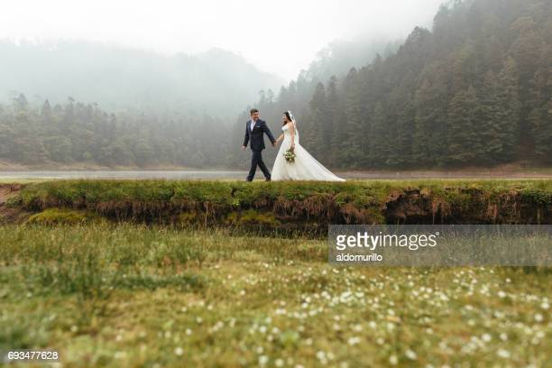 Far shot of newlyweds walking outdoors in foggy day