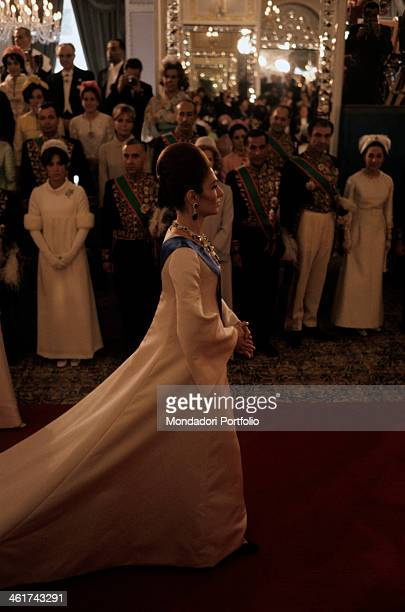 Farah Pahlavi during her coronation day to be the empress of Iran The empress makes her entrance on a red carpet and wears a dress with a long trail...