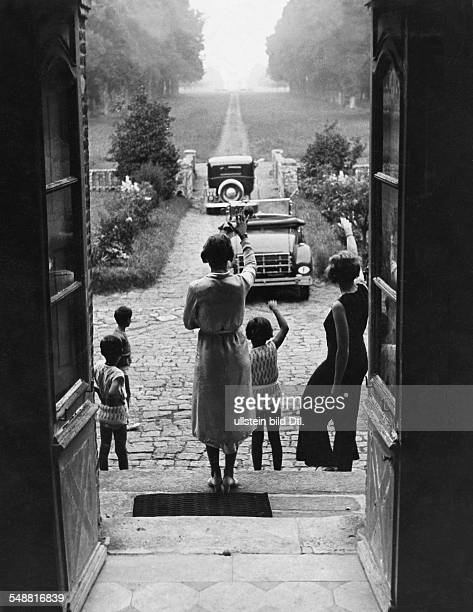 Farewell two women and three children standing at the front door and waving two departing cars Photographer Hug Block 1933 Published by 'Uhu' 09/1933...
