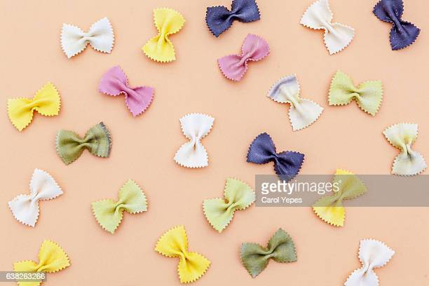 Farfalle pasta random flat lay pattern on color background