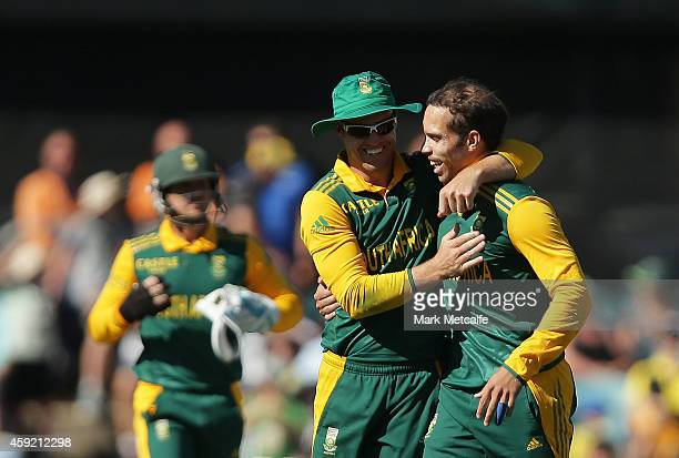 Farhaan Behardien of South Africa celebrates with team mate AB de Villiers after taking the wicket of Shane Watson of Australia during game three of...