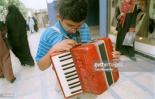 Farhad Sharnazi looks down at the accordion he plays outside the Vanak mall June 11, 2001 on a fashionable street in Tehran, Iran. Life goes on in...