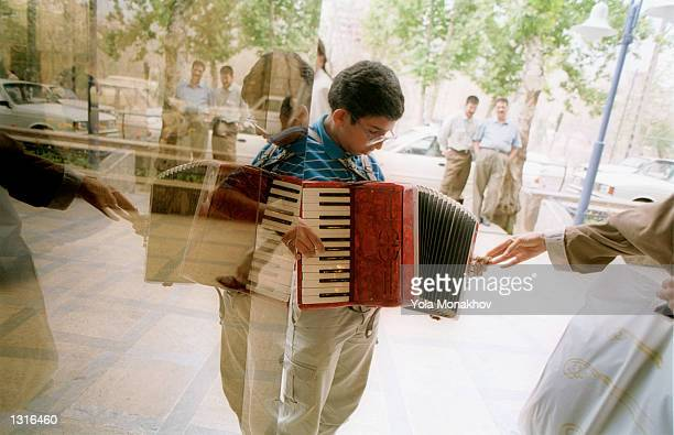 Farhad Sharnazi receives some money from a woman as he plays his accordion outside the Vanak mall June 11, 2001 on a fashionable street in Tehran,...