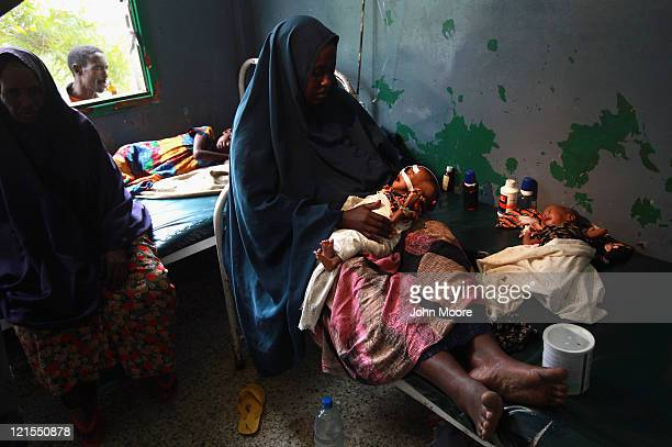 Farhiyo Hassan sits with her sick and malnourished 2-month-old twins at the Banadir hospital on August 20, 2011 in Mogadishu, Somalia. The UN...