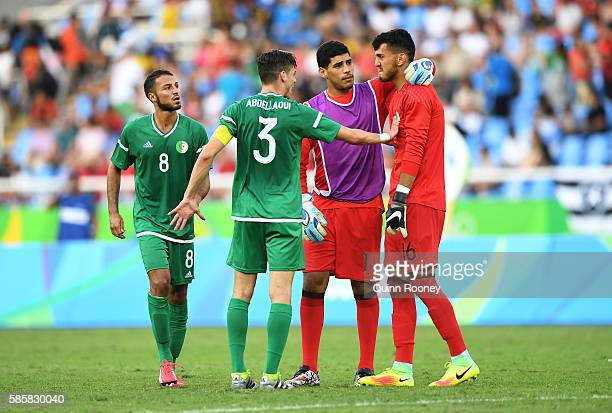 Farid Chaal of Algeria reacts with teammates Abdelkader Salhi Ayoub Abdellaoui and Haris Belkebla after losing the Men's Group D first round match...