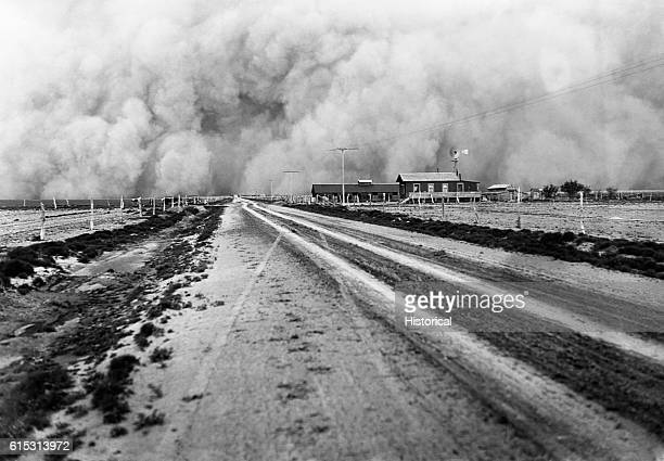 A farm about to be enveloped by a dust storm during the great Dust Bowl of the 1930s